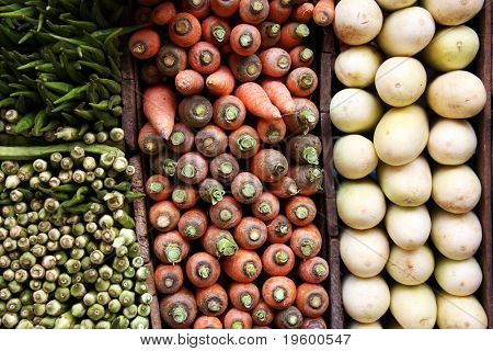 A display of carrots, white aubergines and okra for sale at a Sri Lankan market.