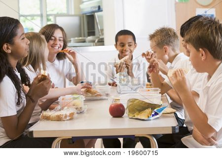 Students sitting at cafeteria table eating lunch