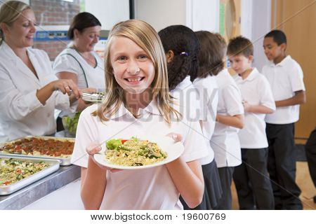 Students in cafeteria line with one holding up her healthy meal and looking at camera