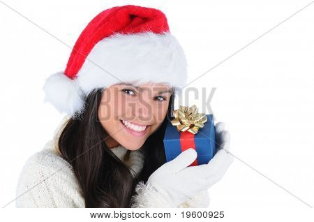 Smiling young woman wearing a Santa Claus hat holding a small Christmas present up to her face. Horizontal format isolated on white.