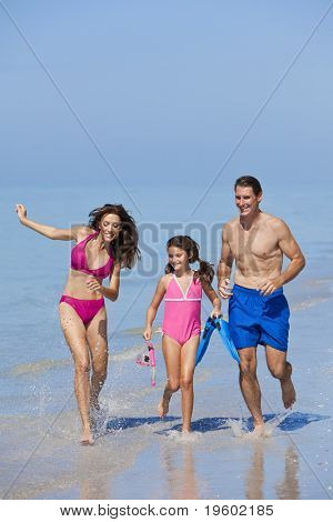A happy family of mother, father and child, a daughter, running holding hands and having fun in the waves of a sunny beach