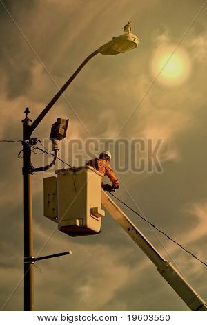 electrician working with dramatic sky background
