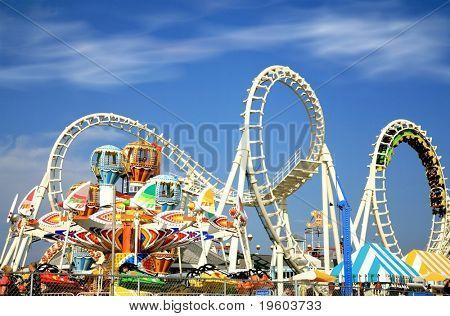Passeios de parque de diversões com um céu muito azul como pano de fundo