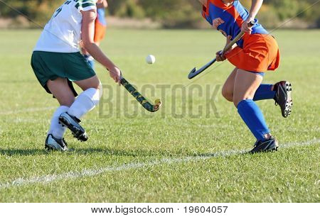 Two girls battle for control of the ball in a field hockey game