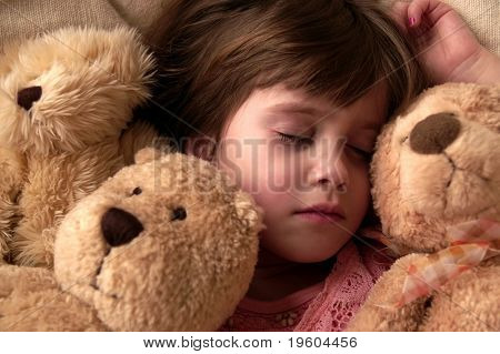 A young girl takes a nap with her teddy bears