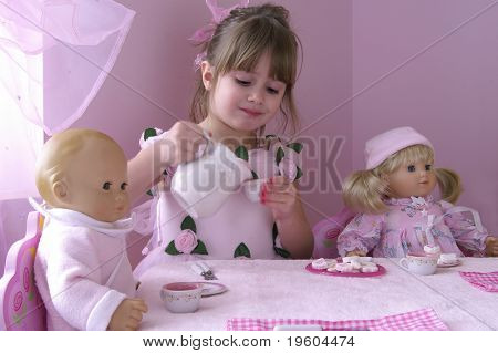 A young girl having a tea party with her baby dolls