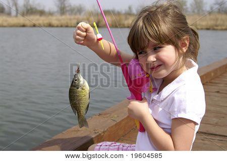 Una niña sostiene un pez que acaba de capturar