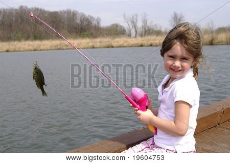 A cute young girl with her fishing pole and the blue-gill she caught