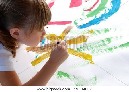 A young girl concentrating on a picture she is painting