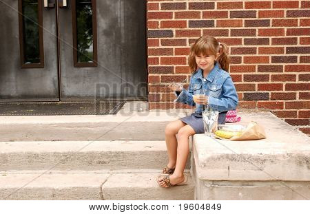 A cute young girl having lunch on the steps of her school