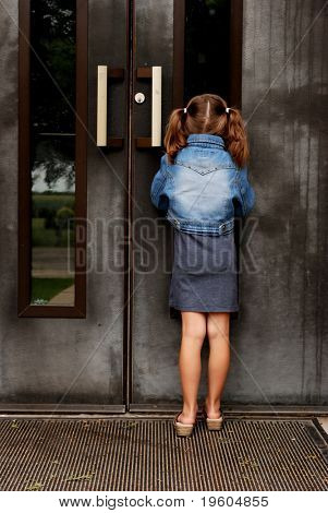 A girl peeking in the window of her school