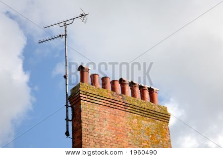 Old British Chimneystack And An Analogue Tv Aerial.
