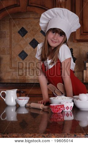 A cute young girl getting ready to bake cupcakes for valentines day