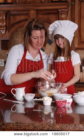 A cute young girl and her mother baking cupcakes together