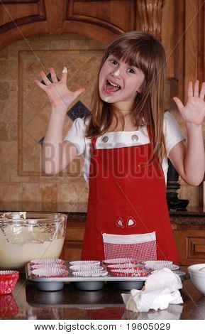 A cute young girl having fun baking cupcakes