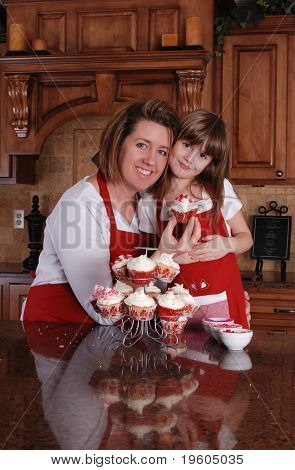 A cute young girl and her mother spending time together baking cupcakes