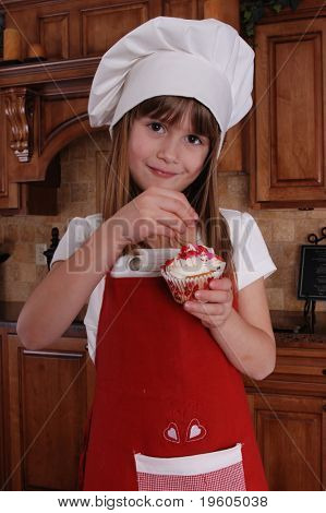 A cute young girl putting sprinkles on her cupcake