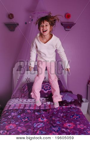 A cute young girl jumping on her bed