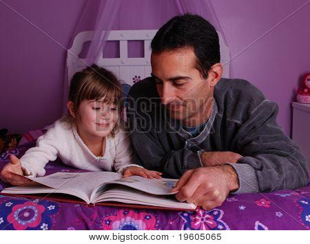 Un padre y una hija pasan tiempo juntos, leyendo un libro