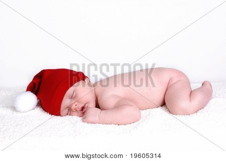 A cute baby sleeping wearing a santa hat