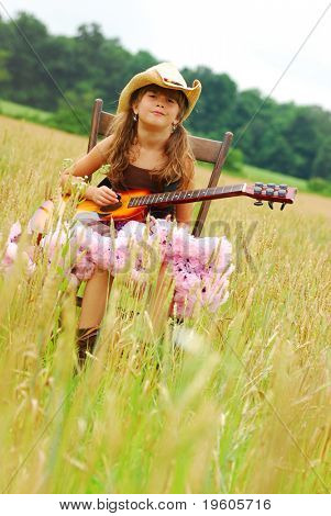 A cute young girl sitting in a field playing the guitar