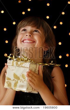 A cute young girl holding a christmas gift,dark background with christmas light bokeh
