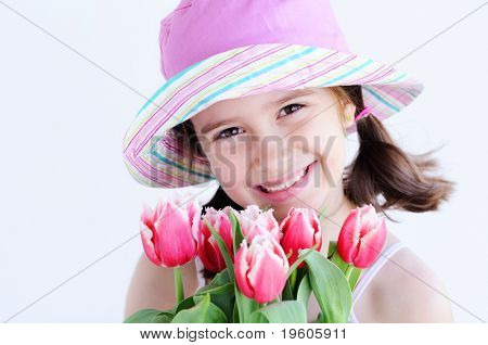 A cute young girl holding a pot of tulips