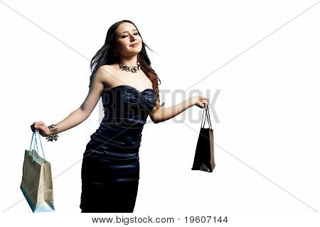 A Beautiful Portrait Of A Young Attractive Woman Holding Shopping Bags. Isolated Over White.