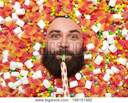 Bearded man all covered with candies blowing in party horn and looking at camera.