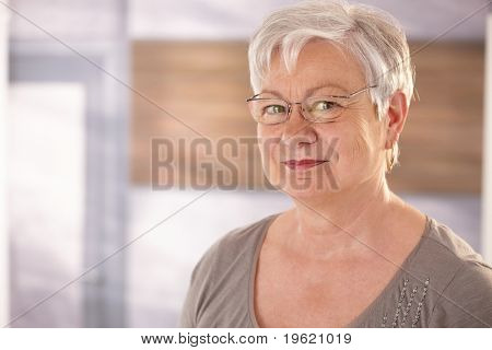 Closeup portrait of happy senior woman with glasses, looking at camera, smiling.?