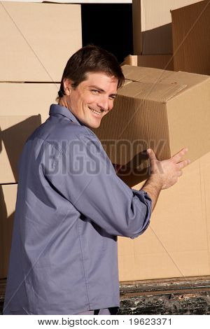 A portrait of a happy mover, moving cardboard boxes