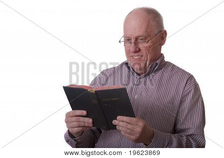 Older Bald Man In Striped Shirt And Glasses Reading Bible