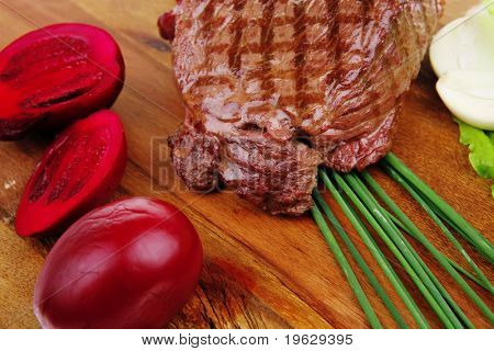 barbecued meat : beef ( lamb ) garnished with green lettuce and red chili hot pepper on wooden plate isolated over white background