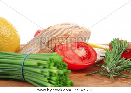 savory sea fish entree : roasted salmon fillet with green onion, red cherry tomatoes pieces,  rosemary twigs and lemon on wooden board isolated on white background . shallow dof