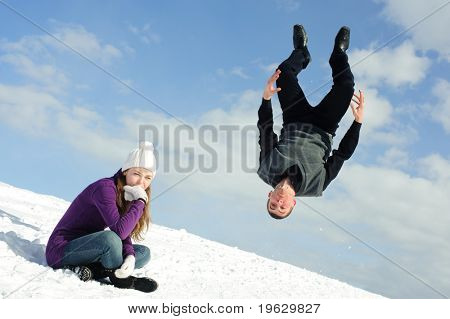Zwei Jugendliche im Feld Schnee, einer von ihnen springen.