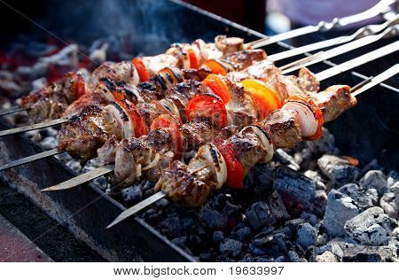 Juicy Slices Of Meat With Sauce Prepare On Fire (shish Kebab).