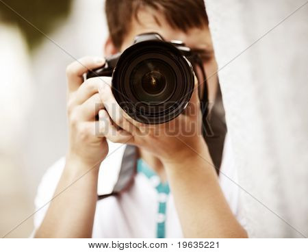 Photographer, selective focus point on nearest part of lens