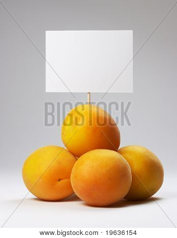 A small heap of apricots with signboard on white background