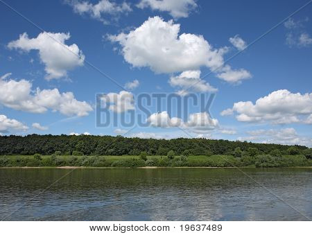 White clouds on blue sky over river