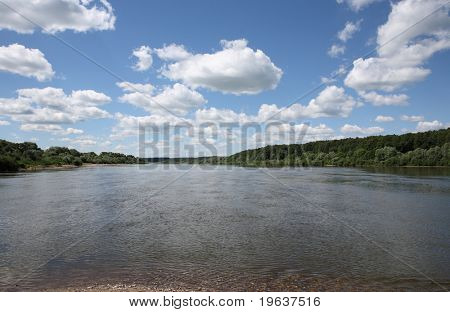 White clouds on blue sky over river (wide angle)