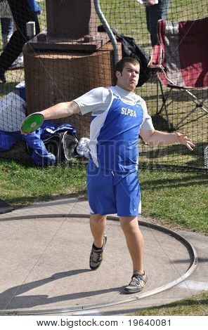 Teen Boy Throwing The Discus At A High School Track And Field Meet