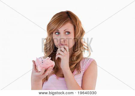 Mulher de cabelos loiros perplexos sobre seu cofrinho quebrado sobre um fundo branco