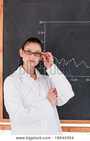 Female scientist standing near the blackboard and looking at the camera