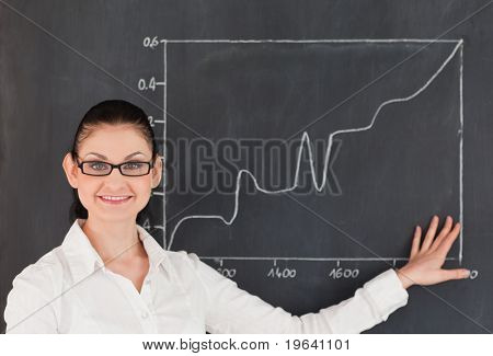 Scientist showing charts while standing near the blackboard in a lab