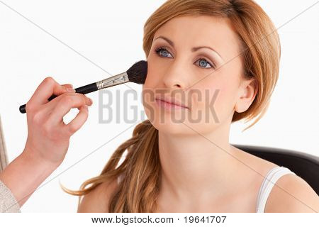 Make-up artist applying make up to a cute blond-haired woman in a studio
