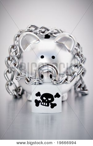 A silver piggy bank chained up with a skull and crossbones padlock on a grey background
