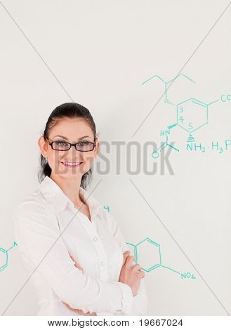 Dark-haired scientist woman looking at the camera while standing in front of a white board