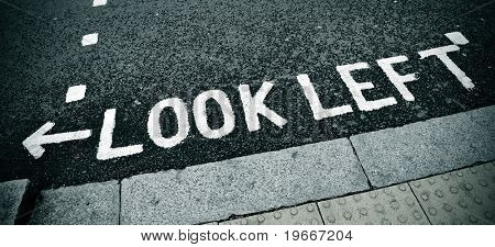look left sign painted on the road