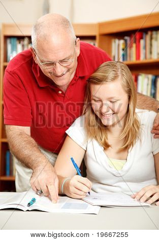 Father helping his teenage daughter study in the library.  Focus on Dad.