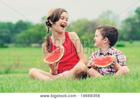 A brother and sister eating watermelon together